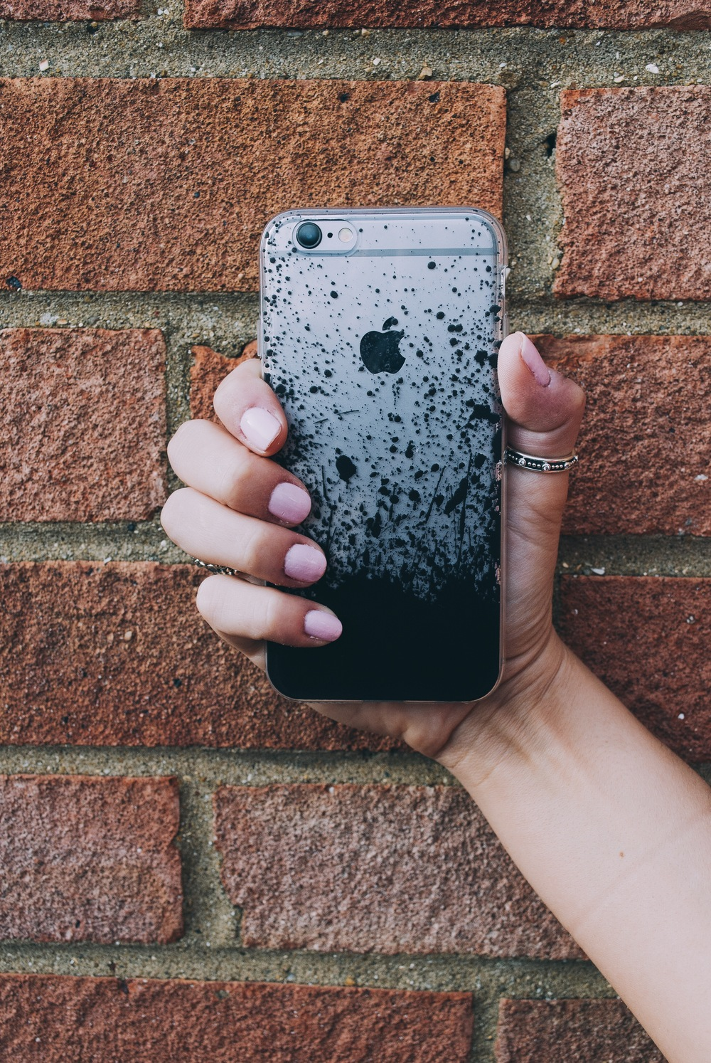 Inkase black paint splat iPhone case against brick wall