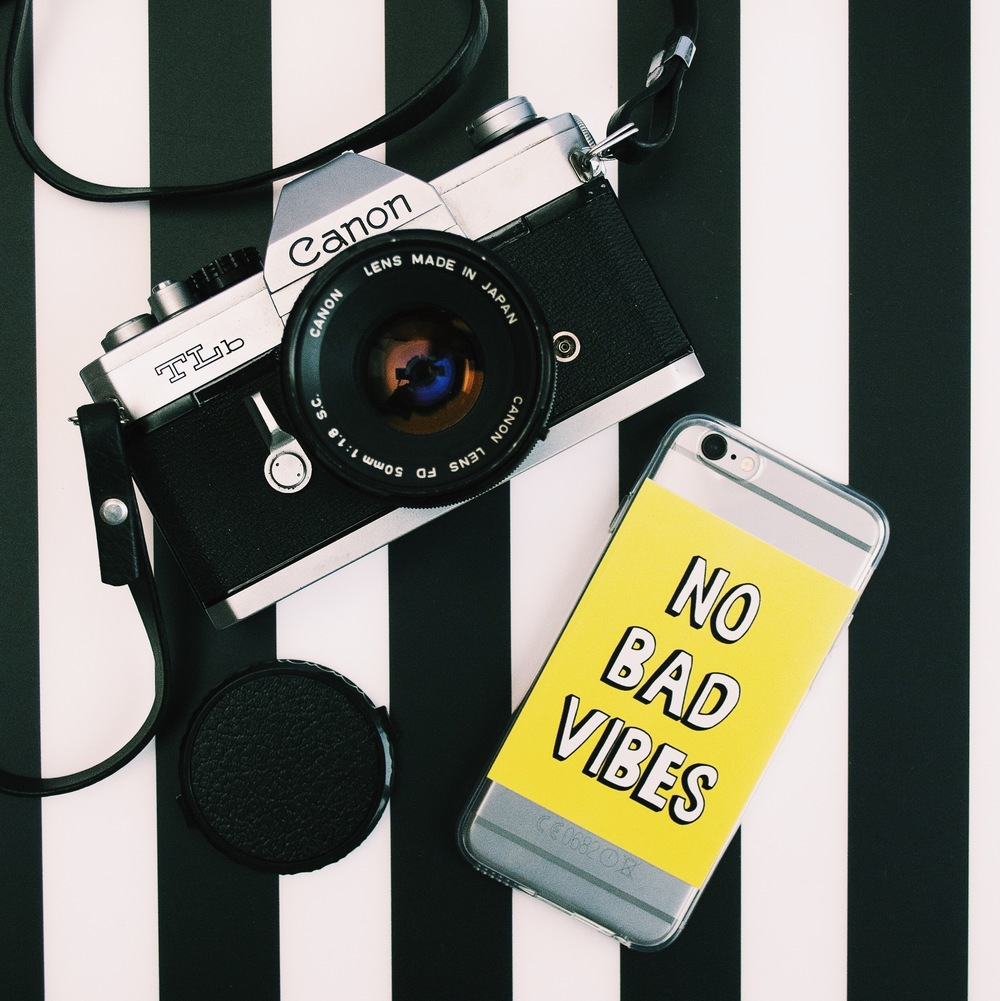 Inkase No Bad VIbes quote phone case on black and white stripe background with canon film camera