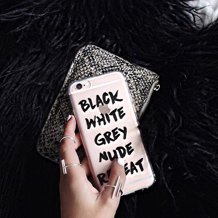 Inkase Black White Grey Nude Repeat iPhone case, held in hand with fashionable rings with leather pouch