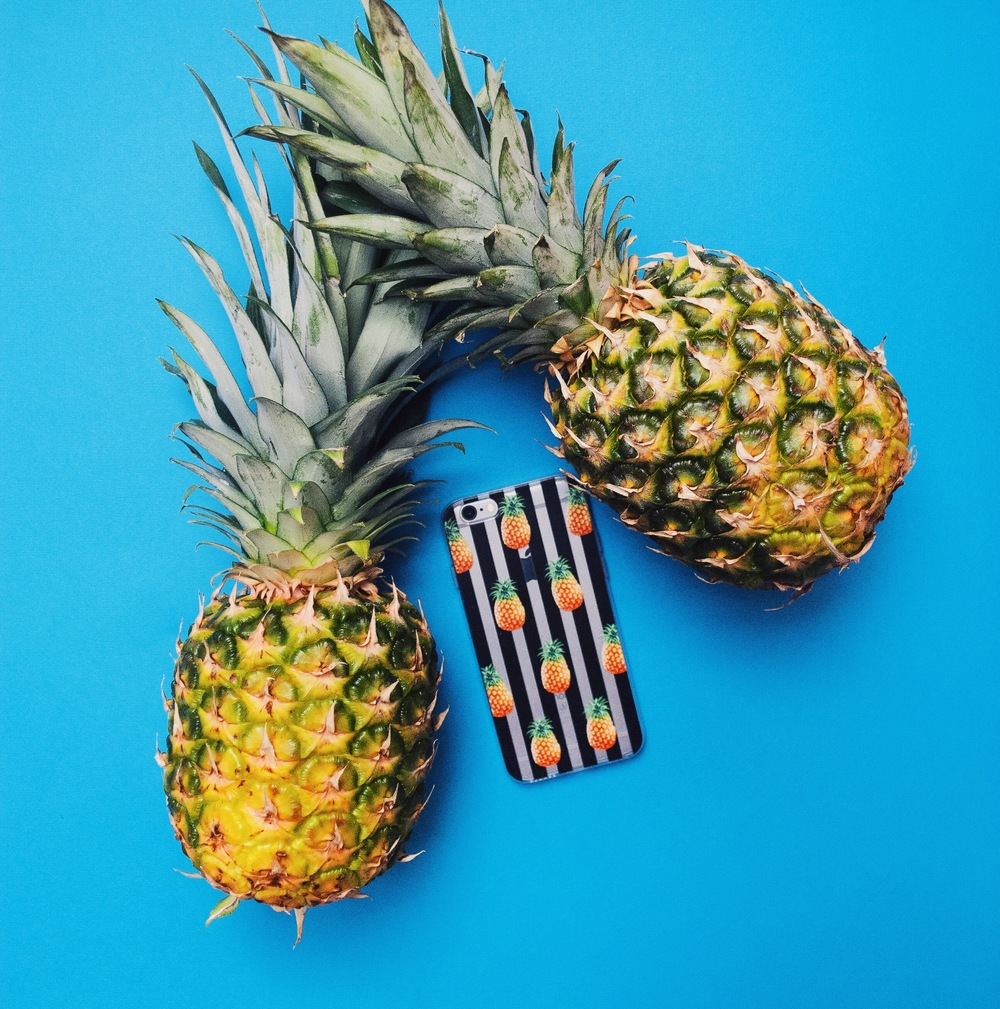 Inkase Pineapple Stripe iPhone case on blue background with 2 pineapples fruit