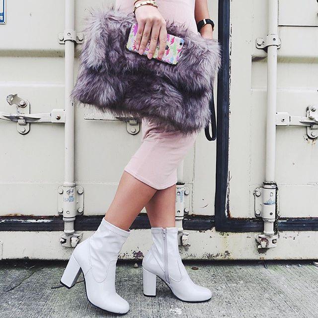 Fashion Blogger Carmen Do on location in fashionable skirt and fluffy bag holding inkase dinosaur phone case