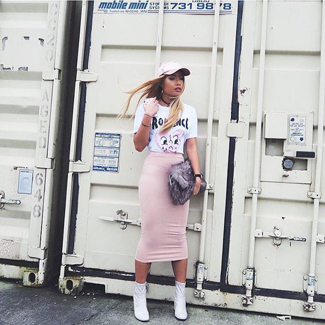Fashion Blogger Carmen Do on location in fashionable shirt and tshirt holding inkase dinosaur phone case