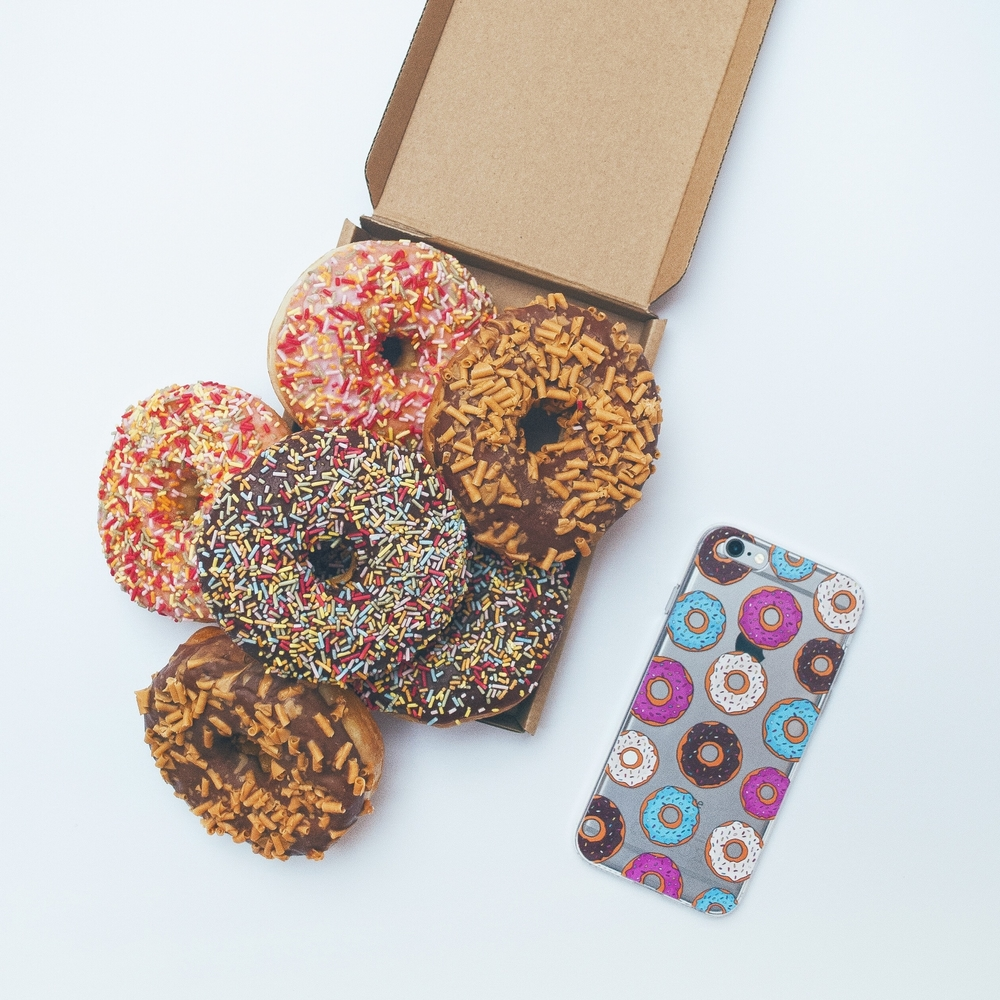 Inkase donut phone case with a pile of donuts in a box