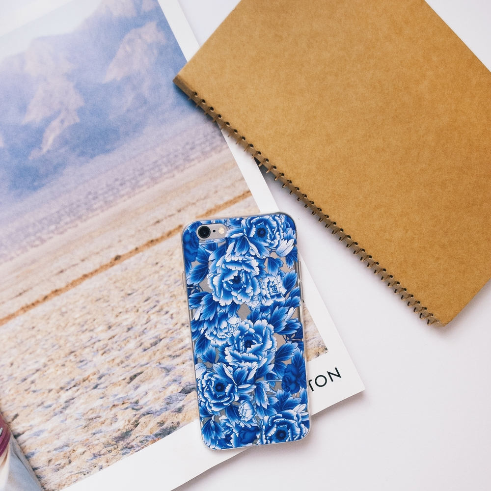 Inkase Blu Flower phone case on desk with a magazine and notebook