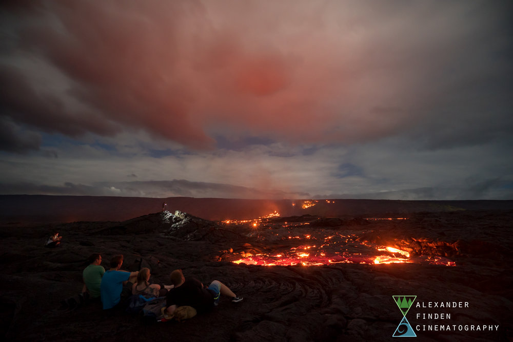 Alex and a few friends sit and watch the lava flow as it slowly approaches overnight.