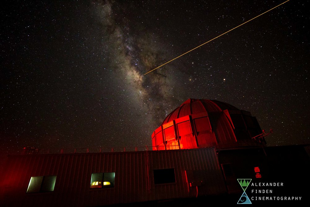 A telescope is lit by a car's break lights as another telescope behind lazes into the galactic center of the Milky Way.