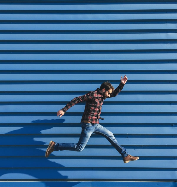 Man jumping representing Work Well Being vision to create healthy happy employees.jpg