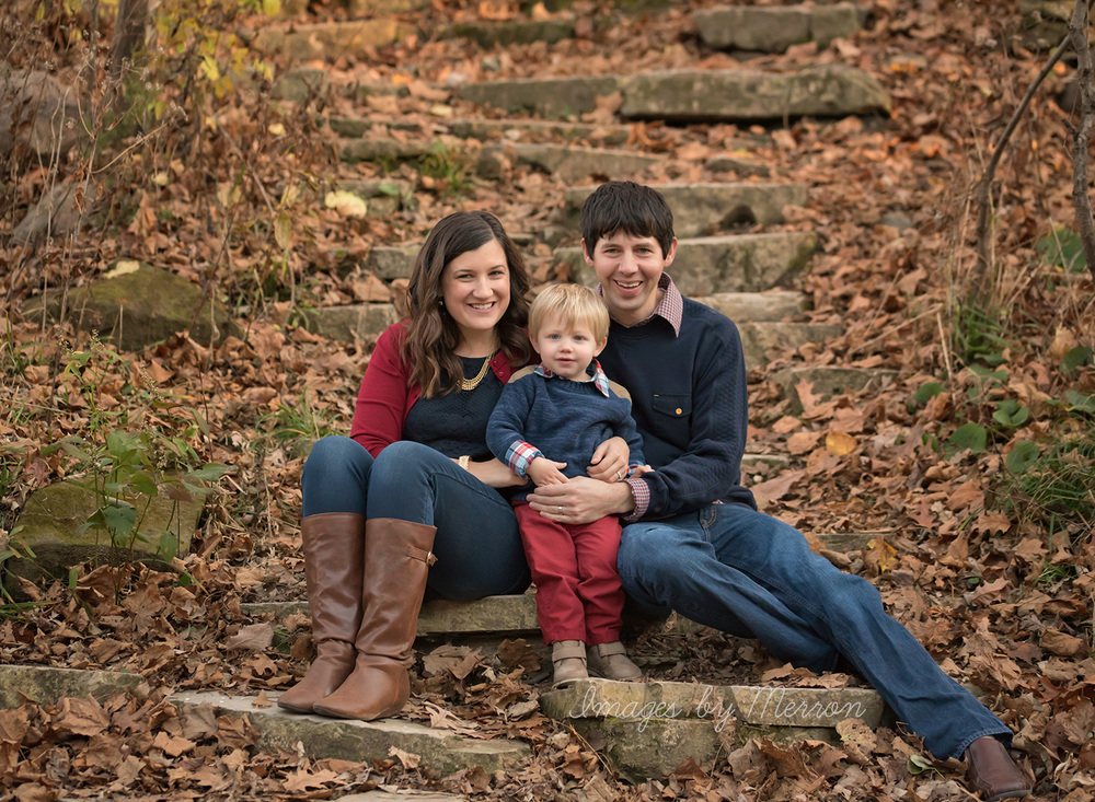 Family with toddler boy posing on rock staircase, smiling