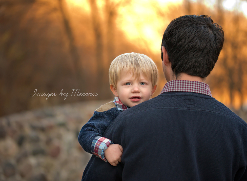 Young boy looking at camera as dad hold him, looking off into sunset