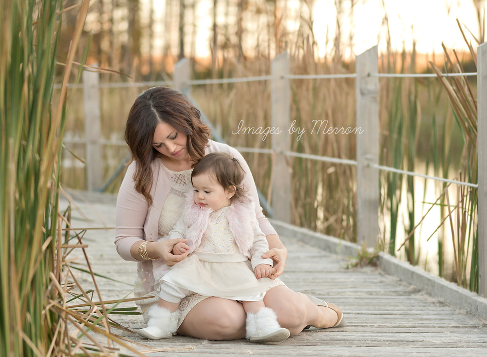 Candid moment between mom and baby girl, sitting on walking bridge