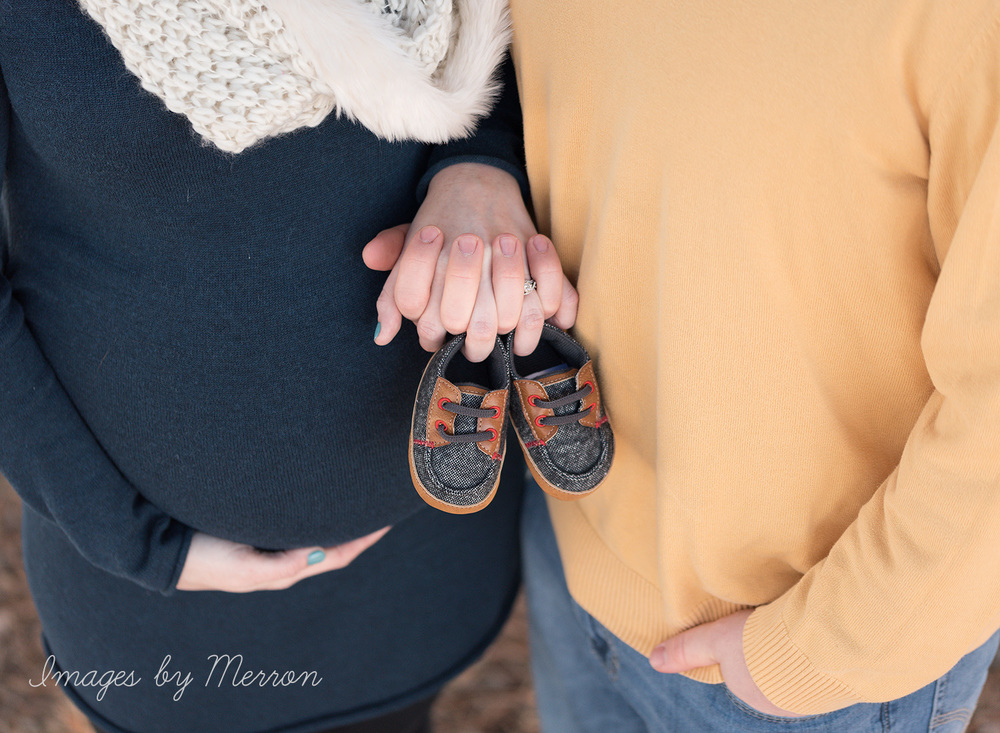 Mom and dad-to-be holding baby boy shoes