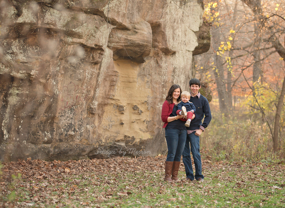 Family of three posing for photo in front of stone wall at Ledges State Park in Iowa