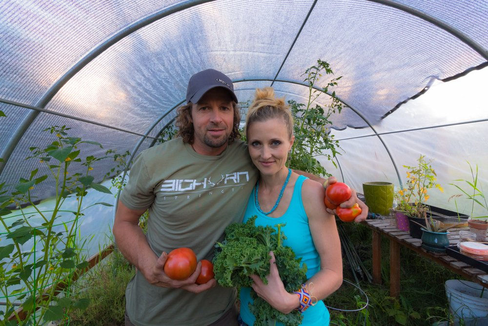 Ryan and Hillary in the greenhouse with a late summer tomato harvest Picture by @_sly_slyvester Ryan's Tshirt @bighornstrength