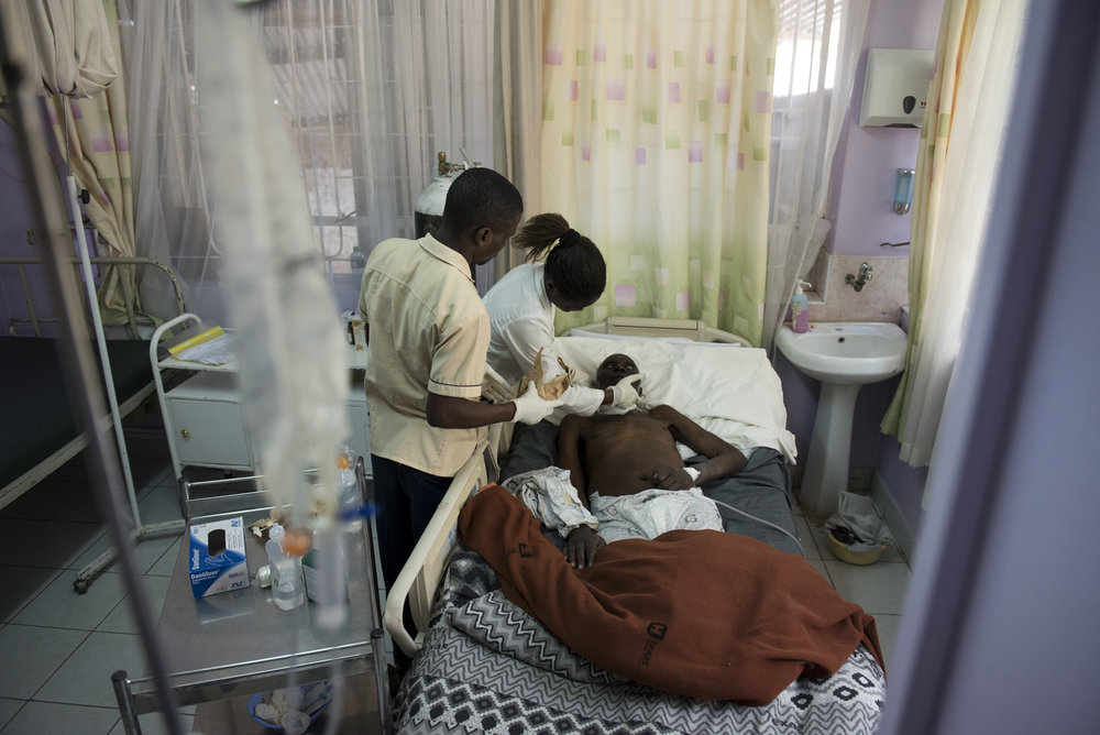 8/24/15 – Nairobi, Kenya – Physician's assistant, Carol Apondi, and her colleague attend to Samwell Mosota Omaiyo, a cancer patient, at the Texas Cancer Center in patient facility in Nairobi, Kenya on Monday, Aug. 24, 2015. Nurses here are trained in palliative care and give round the clock care to over a dozen patients in this small medical building. (Photo by Nicholas Pfosi)