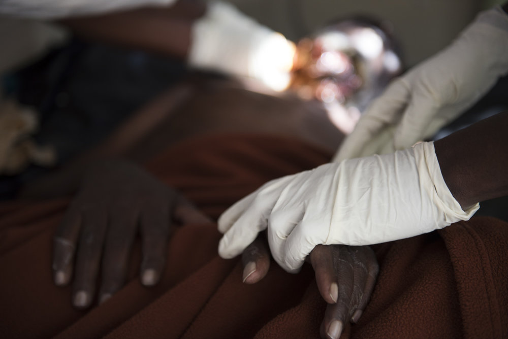 8/22/15 – Nairobi, Kenya – A nurse holds Samwell Mosota Omaiyo's hand during treatment on Saturday afternoon at the Texas Cancer Center in patient facility in Nairobi, Kenya on Saturday, Aug. 22, 2015. Nurses here are trained in palliative care and give round the clock care to over a dozen patients in this small medical building. (Photo by Nicholas Pfosi)