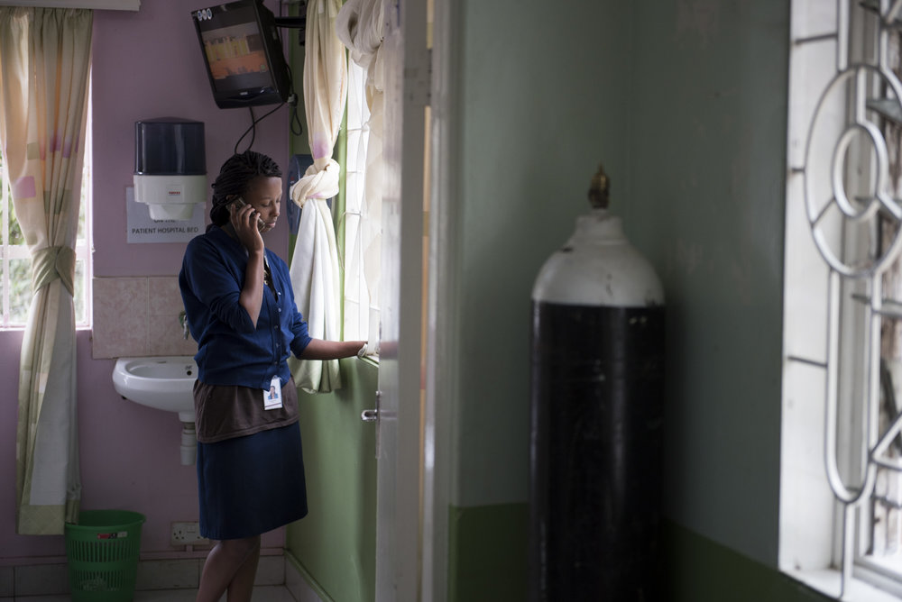 8/25/15 – Nairobi, Kenya – Nurse Milca Mwankiki talks on the phone with a friend at the Texas Cancer Center in patient facility in Nairobi, Kenya on Tuesday, Aug. 25, 2015. Nurses here are trained in palliative care and give round the clock care to over a dozen patients in this small medical building. (Photo by Nicholas Pfosi)
