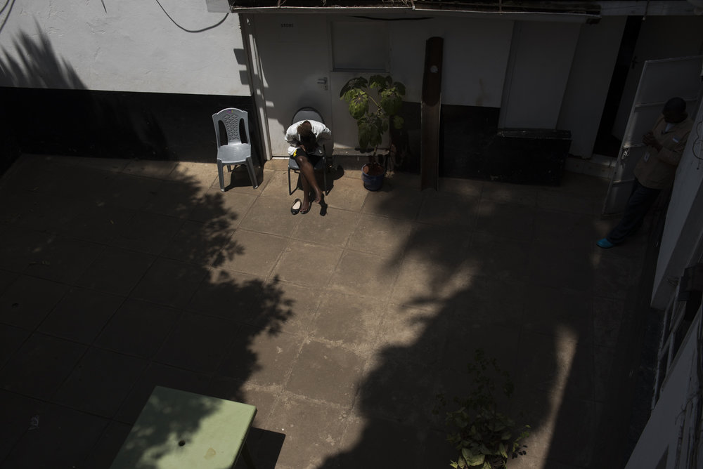 8/27/15 – Nairobi, Kenya – Nurse Carol Apondi relaxes during family visiting hours at the Texas Cancer Center in Nairobi, Kenya on Thursday, Aug. 27, 2015. Nurses here are trained in palliative care and give round the clock care to over a dozen patients in this small medical building. (Photo by Nicholas Pfosi)