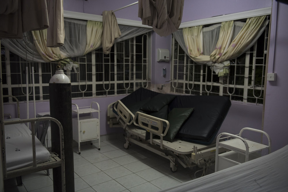 """8/26/15 – Nairobi,  – Samwell Mosota Omaiyo's former bed, approximately an hour after his death due to organ failure at the Texas Cancer Center during the night shift in Nairobi, Kenya on Wednesday, Aug. 26, 2015. Omaiyo was a 52-year old Kenyan with late-stage mandible cancer. He died peacefully. (Photo by Nicholas Pfosi)A palliative care nurse Carren Asembo, attended to him in his final moments and when his wife called to see how her husband was improving, had the responsibility of informing her of his death. When asked about how she was feeling following his loss, Asembo said, """"Nursing is not a job, it's a calling. Those who can't adjust and handle caring for others come, but they soon leave."""""""