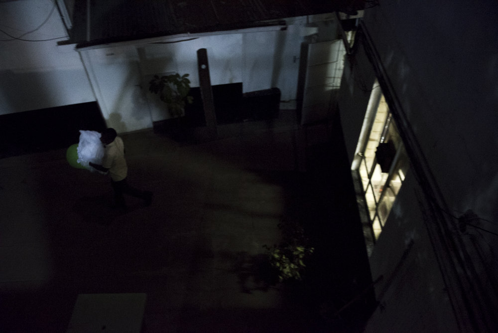 8/26/15 – Nairobi,  – A man brings laundry inside at the Texas Cancer Center during the night shift in Nairobi, Kenya on Wednesday, Aug. 26, 2015. Nurses here are trained in palliative care and give round the clock care to over a dozen patients in this small medical building. (Photo by Nicholas Pfosi)