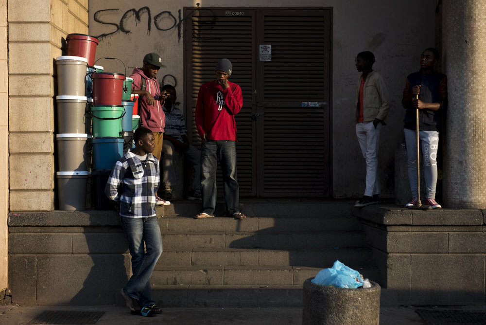 Moth building resident, Matauele Zefanias, in red, smokes a cigarette with other residents outside of the Moth building in the late afternoon in Joubert Park on Tuesday, Aug. 11, 2015.
