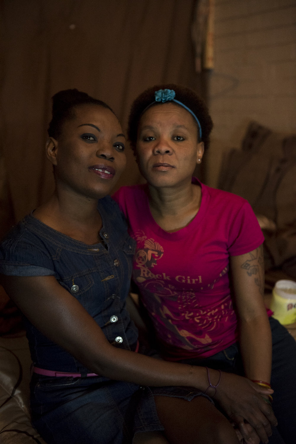 Lufuno Nevhulaudzi poses for a picture with her friend, Yanga Mpengu, a two year resident, in her basement room at the Moth building in Joubert Park on Wednesday, Aug. 5, 2015.