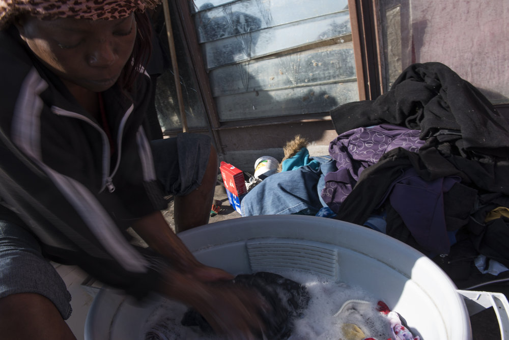 Women do laundry together on the balcony of the Moth building in Joubert Park on Thursday, Aug. 13, 2015.