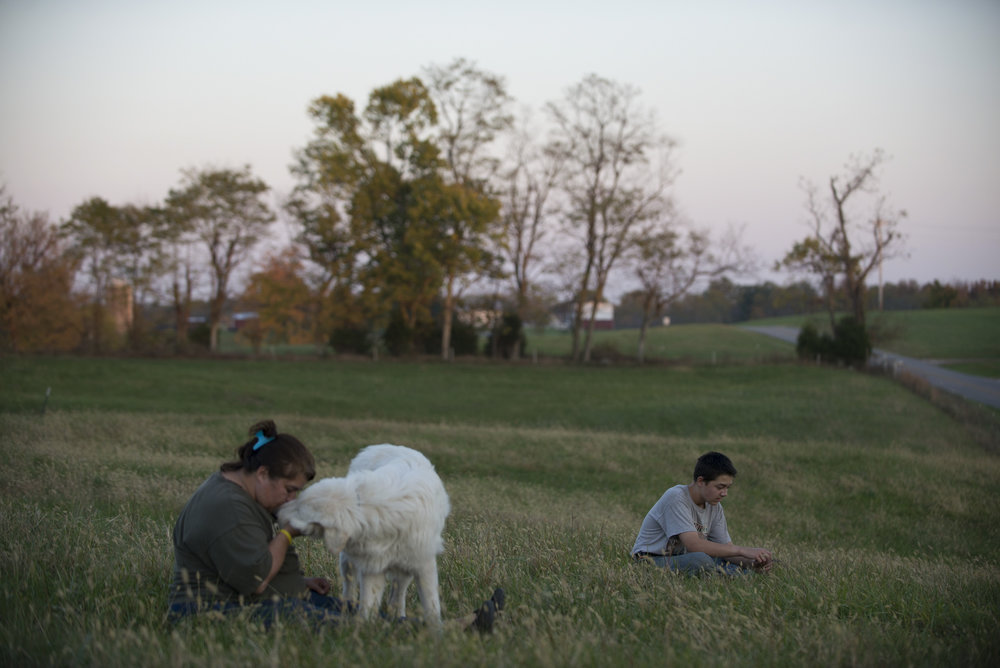Amy rests with Blue and Andrew on the main field after a full day.