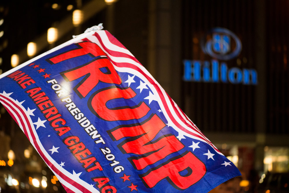 11/9/16 – New York City, MA – A Trump flag during Donald Trump's surprising presidential victory outside the Midtown Hilton Hotel in Manhattan, New York City on Wednesday, Nov. 9, 2016. Following a tumultuous and unusual campaign, candidate Donald Trump surpassed career politician Hilary Clinton in a tight and long election day, with the announcement coming at around 3 o'clock in the morning. (Photo by Nicholas Pfosi)