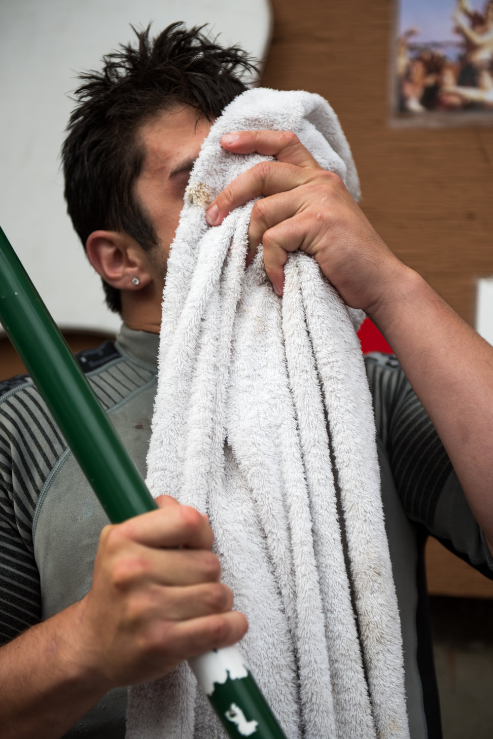 Gloucester, MA - 6/25/17 - Jack Wagner toweling off his face after his Sunday greasy pole event win during the St. Peter's Fiesta in Gloucester, Mass. on Sunday, June 25, 2017. Each year a select group of men, some novices, others seasoned champions, compete against each other to see who can run across a telephone pole layered in grease and suspended over the sea. This year after one full round, Gloucester resident, Jake Wagner, grabbed the flag, claiming victory. (Nicholas Pfosi for The Boston Globe) Reporter: Billy Baker Topic: 02greasypole(2)