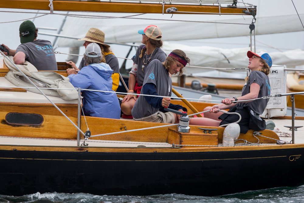 Brooklin, ME - 8/5/17 - Ethan winches in the jib following a tack during the start sequence while his cousin Emma Conover tails during the Eggemoggin Reach Regatta on Saturday, August 5, 2017. The Conover clan has come together for years to race in the Eggemoggin Reach Regatta. (Nicholas Pfosi for The Boston Globe) Reporter: Bethany Ao Topic: woodenboatEmma Conover, 23; tall, skinny, often wear hatsEthan Andrus, 15; Jen's son, long hair, often has headband, biked downJen Conover; mother, biked downLydia Morin, 20; niece of Jen, biked down, has straw hat on SinbadDee Dee Conover, 82; 82 years oldElli Andrus, 12; Ethan's sister; youngest, blonde hairSimon Morin, 18; Lydia's brother, longer hair, tallCedar Andrus; not a lot of photos of him, blonde hair, shorterWill Conover, 21; tallest, Peace Corps guy, curly hair