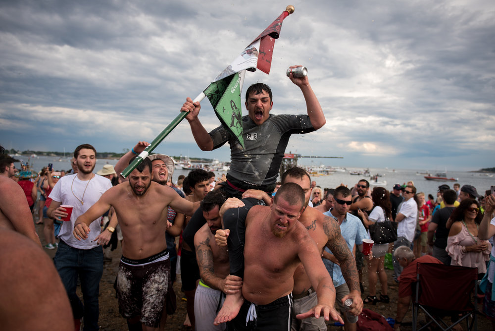 Gloucester, MA - 6/25/17 - Jack Wagner celebrating his Sunday greasy pole event win during the St. Peter's Fiesta in Gloucester, Mass. on Sunday, June 25, 2017. Each year a select group of men, some novices, others seasoned champions, compete against each other to see who can run across a telephone pole layered in grease and suspended over the sea. This year after one full round, Gloucester resident, Jake Wagner, grabbed the flag, claiming victory. (Nicholas Pfosi for The Boston Globe) Reporter: Billy Baker Topic: 02greasypole(2)