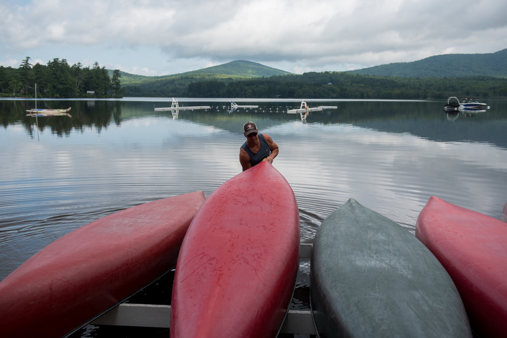 Orford, NH - 7/18/17 - Bill Miller flips a canoe before taking campers out wake surfing during a sunny morning at Camp Moosilauke on Tuesday, July 18, 2017. Camp Moosilauke is the oldest continually operated camp in New Hampshire, founded in 1904. (Nicholas Pfosi for The Boston Globe) Reporter: Tom Farragher Topic: 19Farragher