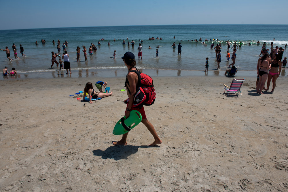 Hampton, NH - 7/21/17 - Lifeguard James Kelly patrols the beach during a sunny Friday afternoon at Hampton Beach on Friday, July 21, 2017. Early this week dozens of rescues occurred due to strong rip tides, an unusually high number. (Nicholas Pfosi for The Boston Globe) Reporter: Billy Baker Topic: 22rescues(2)