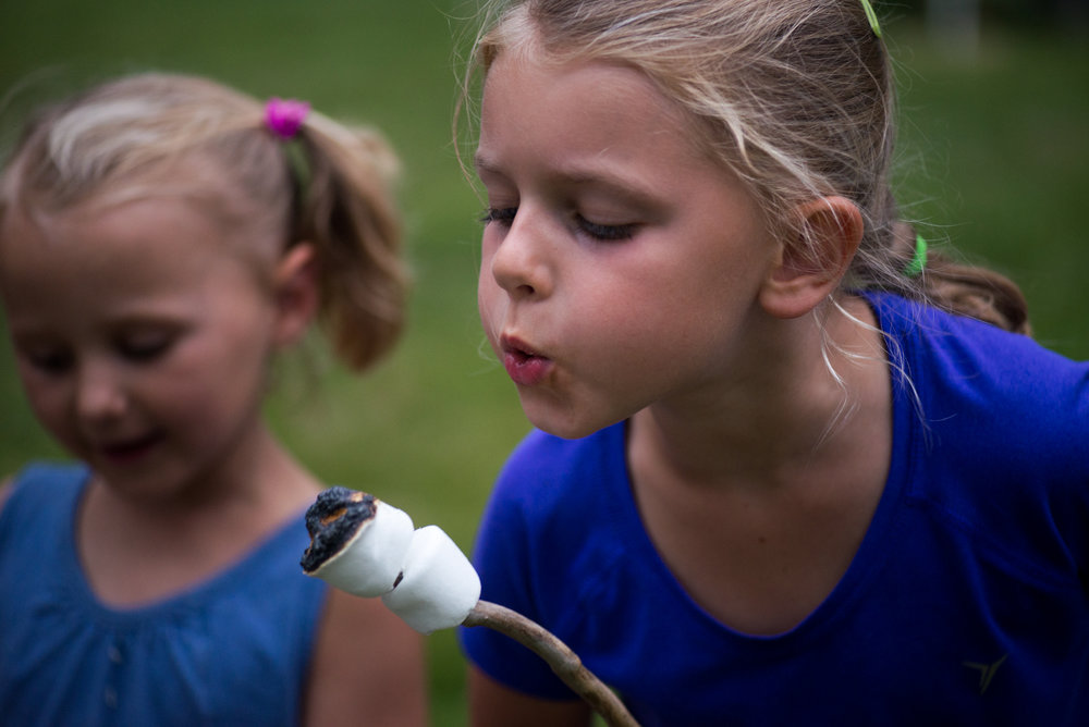 Hingham, MA - 7/22/17 - Rachel Oliwa blows out a flaming marshmallow during the annual World End's Reservation overnight camping event on Saturday, July 22, 2017. The Trustees of Reservations normally prohibits overnight camping on this land but once a year members are allowed to spend a night out in nature with their families. (Nicholas Pfosi for The Boston Globe) Reporter: Brion O'Connor Topic: 30zorec(2)