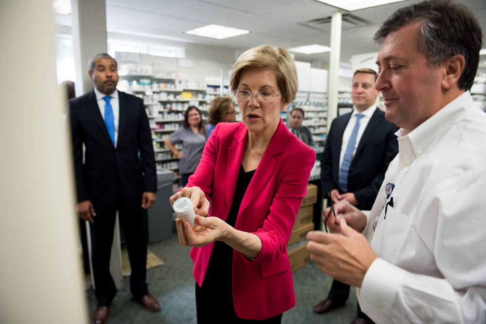Boston, MA - 7/31/17 - Senator Elizabeth Warren talks with Donato Mazzola, the Pharmacy Operations Manager, about an automatic prescription filling machine during a tour of East Boston Neighborhood Health Center (EBNHC), one of the largest community health centers in the country, on Monday, July 31, 2017. The tour of the facility was followed by a roundtable discussion with EBNHC leadership, providers, and local elected officials about the fight for healthcare in the legislature. (Nicholas Pfosi for The Boston Globe) Reporter: Claire Parker Topic: 01warrenpic