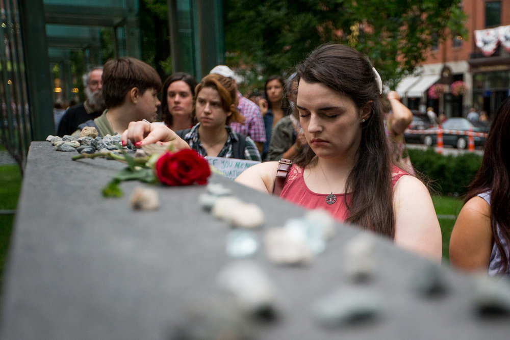Boston, MA - 8/15/17 - Sallie Bieterman, an Emerson student from Seattle, places a rock during a vigil at the Holocaust Memorial in downtown Boston on Tuesday, August 15, 2017. The vigil was vandalized yesterday when a Malden teenager shattered one of the memorial's panes of glass, which is the second act this summer. (Nicholas Pfosi for The Boston Globe) Topic: 16memorial(4)