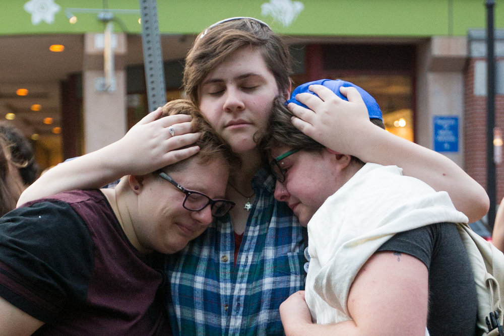 Boston, MA - 8/15/17 - From left to right, Sasha Kaufman, Roni Simcha Miller and August Eberlein, embrace after a vigil at the Holocaust Memorial in downtown Boston on Tuesday, August 15, 2017. The vigil was vandalized yesterday when a Malden teenager shattered one of the memorial's panes of glass, which is the second act this summer. (Nicholas Pfosi for The Boston Globe) Topic: 16memorial(4)