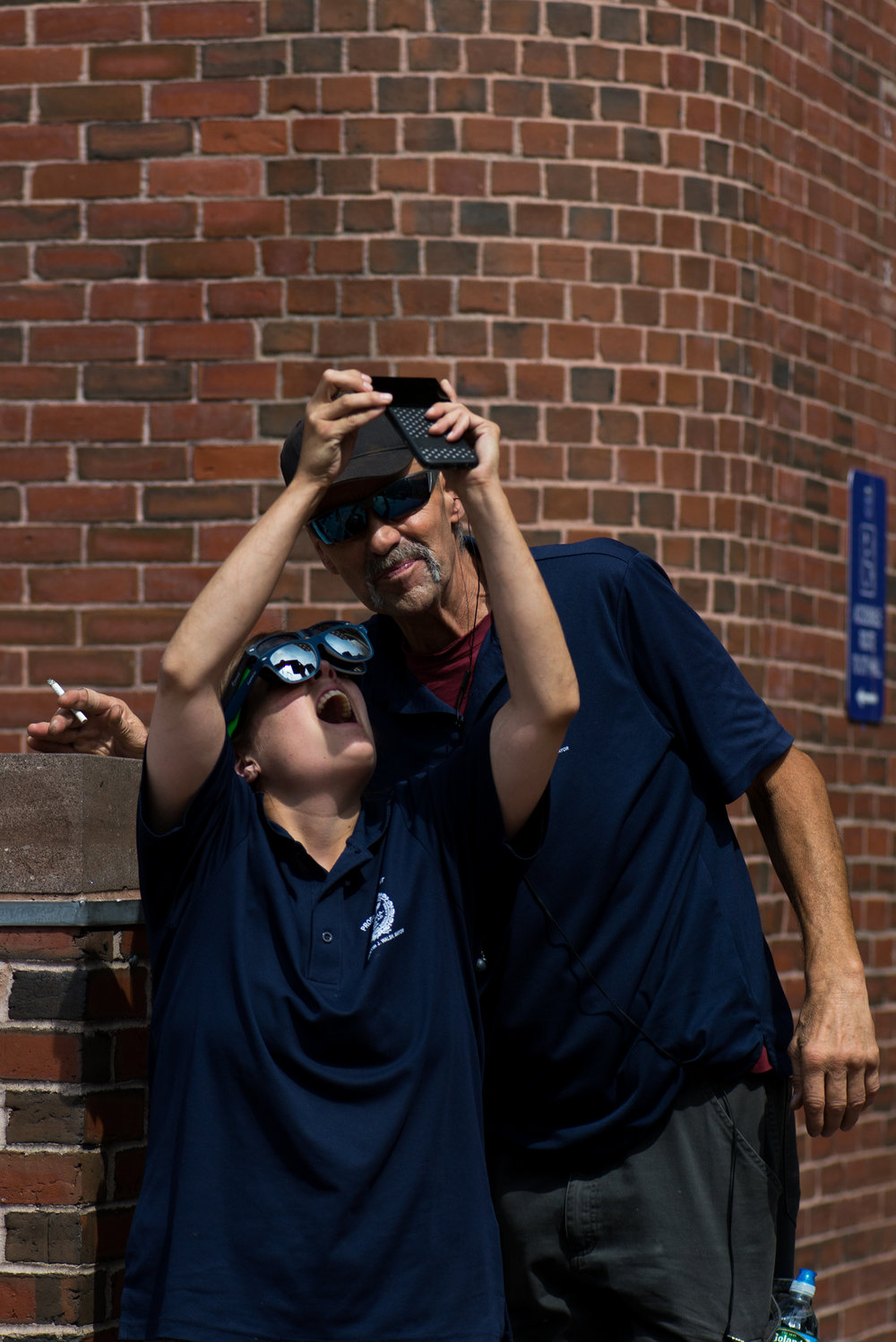 Boston, MA - 8/21/17 - A woman who declined to be identified and Tony Holm photograph the eclipse during the partial solar eclipse in City Hall Plaza on Monday, August 21, 2017. (Nicholas Pfosi for The Boston Globe) Topic: 22eclipsepic