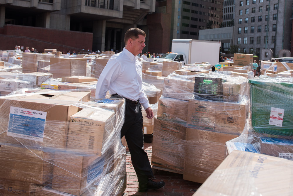 Boston, MA - 9/1/17 - Boston Mayor Marty Walsh walks among packed boxes of goods during a rush to sort and package donated supplies to Hurricane Harvey victims in Houston, Texas on the Boston City Hall Plaza on Friday, September 1, 2017. (Nicholas Pfosi for The Boston Globe) Reporter: John Ellement Topic: 02cityhall