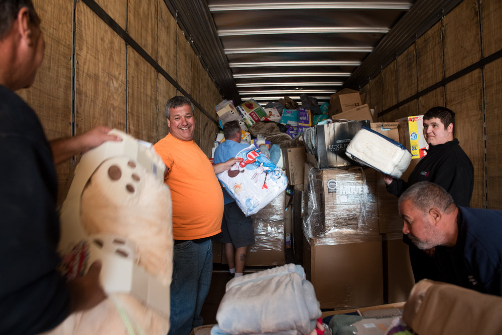 Boston, MA - 9/1/17 - Kevin Velez of Lawton Welding, in orange, loads his company's truck with the help of his son, far right, and volunteers from the Boston Housing Authority and Boston Public Works during a rush to sort and package donated supplies to Hurricane Harvey victims in Houston, Texas on the Boston City Hall Plaza on Friday, September 1, 2017. (Nicholas Pfosi for The Boston Globe) Reporter: John Ellement Topic: 02cityhall