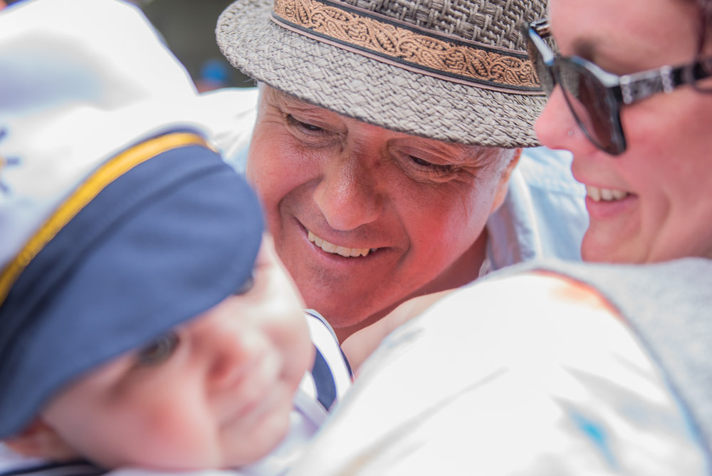 Gloucester, MA - 6/25/17 - [AWAITING ID FROM REPORTER] admires a baby during the St. Peter's Fiesta in Gloucester, Mass. on Sunday, June 25, 2017. Each year a select group of men, some novices, others seasoned champions, compete against each other to see who can run across a telephone pole layered in grease and suspended over the sea. This year after one full round, Gloucester resident, Jake Wagner, grabbed the flag, claiming victory. (Nicholas Pfosi for The Boston Globe) 