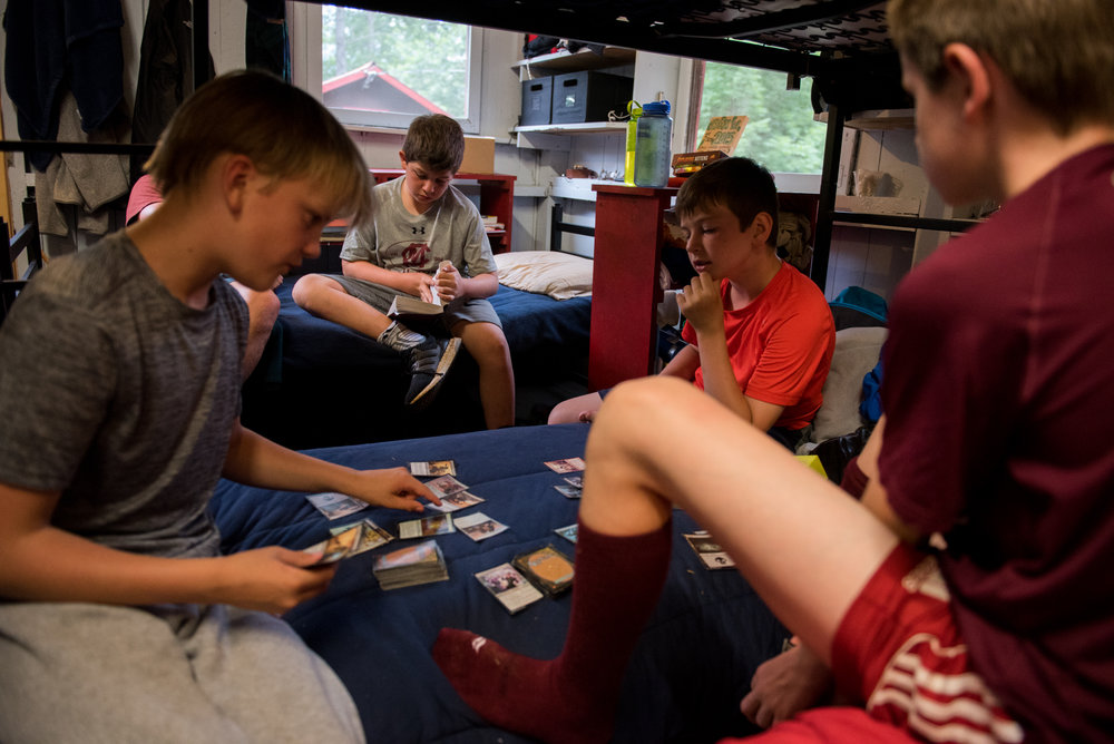 Orford, NH - 7/17/17 - Center, camper Carson Krulewitch, reads The Mark of Athena while his fellow campers play Magic the Gathering during a rainy afternoon at Camp Moosilauke on Monday, July 17, 2017. Because of the weather, the power was temporarily knocked out but campers continued on with flash lights, hardly missing a beat. (Nicholas Pfosi for The Boston Globe) 
