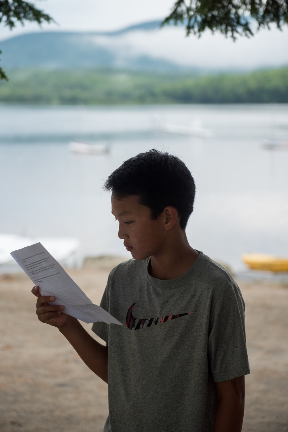 Orford, NH - 7/17/17 - Bobby Kwon, whose birthday was today, reads a letter during a rainy afternoon at Camp Moosilauke on Monday, July 17, 2017. Because of the weather, the power was temporarily knocked out but campers continued on with flash lights, hardly missing a beat. (Nicholas Pfosi for The Boston Globe) 