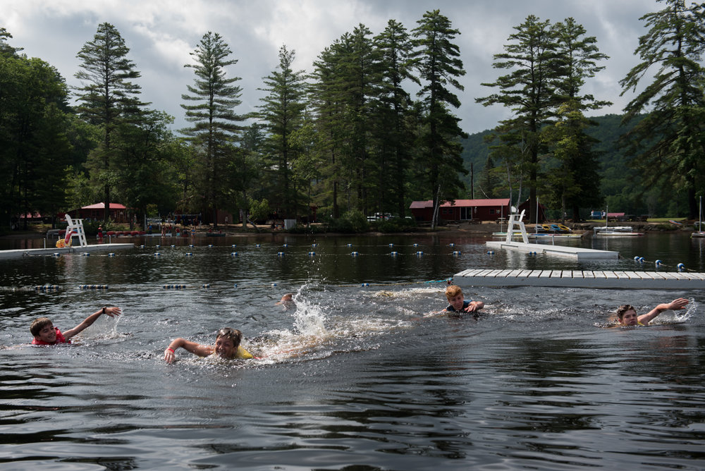 Orford, NH - 7/18/17 - Campers swim out to the speedboat for wake surfing during a sunny morning at Camp Moosilauke on Tuesday, July 18, 2017. Camp Moosilauke is the oldest continually operated camp in New Hampshire, founded in 1904. (Nicholas Pfosi for The Boston Globe) 