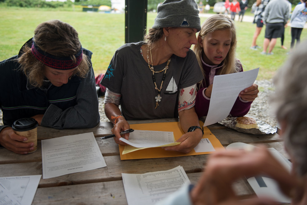 Brooklin, ME - 8/5/17 - Jen, center, listens to her daughter Elli during the skippers meeting in the main event structure on the Wooden Boat School grounds in Brooklin on Saturday, August 5, 2017. The Conover clan has come together for years to race in the Eggemoggin Reach Regatta. (Nicholas Pfosi for The Boston Globe) Reporter: Bethany Ao Topic: woodenboatEmma Conover, 23; tall, skinny, often wear hatsEthan Andrus, 15; Jen's son, long hair, often has headband, biked downJen Conover; mother, biked downLydia Morin, 20; niece of Jen, biked down, has straw hat on SinbadDee Dee Conover, 82; 82 years oldElli Andrus, 12; Ethan's sister; youngest, blonde hairSimon Morin, 18; Lydia's brother, longer hair, tallCedar Andrus; not a lot of photos of him, blonde hair, shorterWill Conover, 21; tallest, Peace Corps guy, curly hair