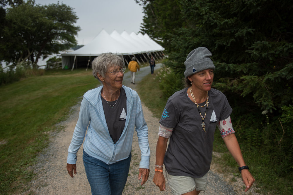 Brooklin, ME - 8/5/17 - Deedee, left, and Jen, right, walk up before the skippers meeting in the main event structure on the Wooden Boat School grounds in Brooklin on Saturday, August 5, 2017. The Conover clan has come together for years to race in the Eggemoggin Reach Regatta. (Nicholas Pfosi for The Boston Globe) Reporter: Bethany Ao Topic: woodenboatEmma Conover, 23; tall, skinny, often wear hatsEthan Andrus, 15; Jen's son, long hair, often has headband, biked downJen Conover; mother, biked downLydia Morin, 20; niece of Jen, biked down, has straw hat on SinbadDee Dee Conover, 82; 82 years oldElli Andrus, 12; Ethan's sister; youngest, blonde hairSimon Morin, 18; Lydia's brother, longer hair, tallCedar Andrus; not a lot of photos of him, blonde hair, shorterWill Conover, 21; tallest, Peace Corps guy, curly hair