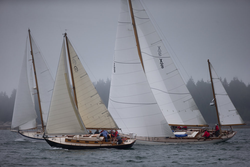 Brooklin, ME - 8/5/17 - Sinbad, black, beats upwind with two boats to windward during the Eggemoggin Reach Regatta on Saturday, August 5, 2017. The Conover clan has come together for years to race in the Eggemoggin Reach Regatta. (Nicholas Pfosi for The Boston Globe) Reporter: Bethany Ao Topic: woodenboatEmma Conover, 23; tall, skinny, often wear hatsEthan Andrus, 15; Jen's son, long hair, often has headband, biked downJen Conover; mother, biked downLydia Morin, 20; niece of Jen, biked down, has straw hat on SinbadDee Dee Conover, 82; 82 years oldElli Andrus, 12; Ethan's sister; youngest, blonde hairSimon Morin, 18; Lydia's brother, longer hair, tallCedar Andrus; not a lot of photos of him, blonde hair, shorterWill Conover, 21; tallest, Peace Corps guy, curly hair