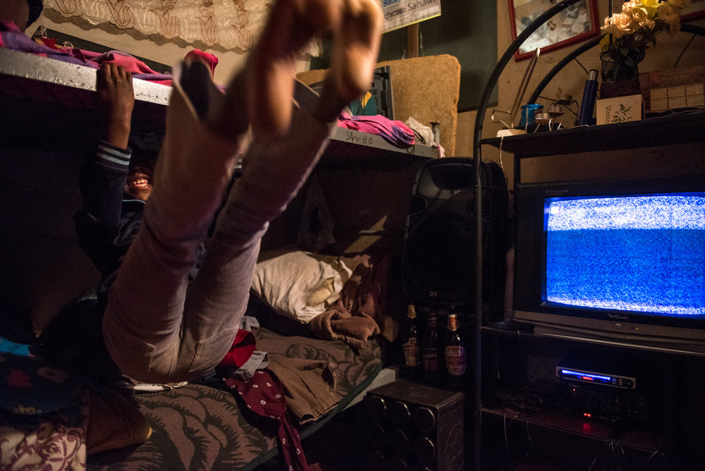 8/11/15 – Johannesburg, South Africa – Madeleine Cossa, 8, swings on her bunkbed in their apartment in the Moth building in Joubert Park on Tuesday, Aug. 11, 2015. The residents here were evicted from their previous building in New Town to make way for a new mall under construction. (Photo by Nicholas Pfosi for The Mail & Guardian)
