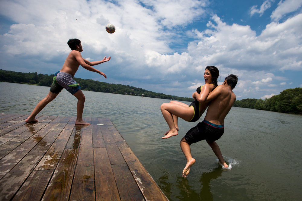 Medford, MA - 6/23/17 - James Garcia, 17, of Malden High School pulls Isabelli (cq) Pereira, 17, of Everett High School into the water while Emanuel Martinez, 15, of Medford High School tosses a soccer ball at the Tufts Larry Bacow Sailing Pavillion on Mystic Lake on Friday, June 23, 2017. The temperature today exceeded 90 degrees. (Nicholas Pfosi for The Boston Globe) Gabriel James, 18, of Everett High SchoolIsabelli (cq) Pereira, 17, of Everett High SchoolJames Garcia, 17, of Malden High SchoolEmanuel Martinez, 15, of Medford High School