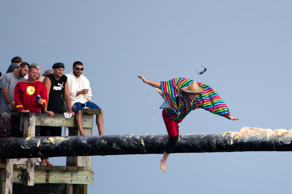 Gloucester, MA - 6/25/17 - A man slips and falls off the greasy pole during the St. Peter's Fiesta in Gloucester, Mass. on Sunday, June 25, 2017. Each year a select group of men, some novices, others seasoned champions, compete against each other to see who can run across a telephone pole layered in grease and suspended over the sea. This year after one full round, Gloucester resident, Jake Wagner, grabbed the flag, claiming victory. (Nicholas Pfosi for The Boston Globe) Reporter: Billy Baker Topic: 02greasypole(2)